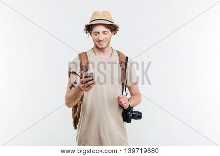 Portrait of a smiling young man with backpack and camera using smart phone isolated on a white background