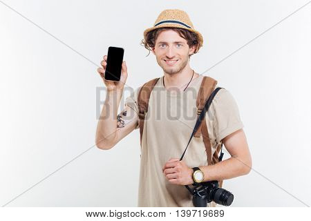 Young smiling happy man showing smart phone with blank screen isolated on a white background