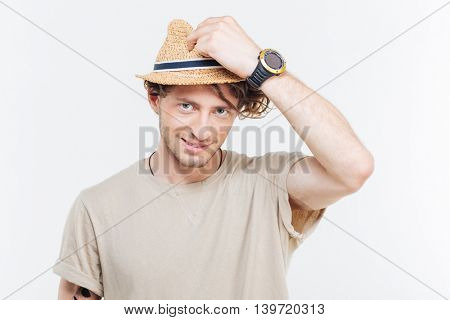 Cheerful attractive young man in hat looking at camera over white background