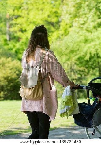Happy mother walking with baby stroller in park