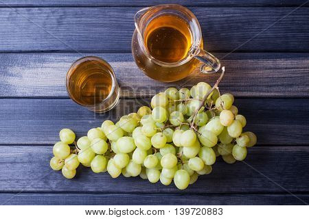 bunch of grapes and a pitcher of grape juice on dark wooden background