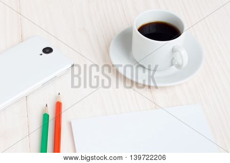 A Cup of coffee a notebook a smartphone pencils on a wooden table