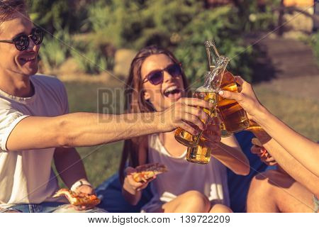 Young beautiful people in casual clothes and sun glasses are clinking bottles and laughing while resting outdoors