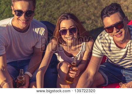 Portrait of young beautiful people in casual clothes and sun glasses holding bottles of beverage looking at camera and smiling while resting outdoors