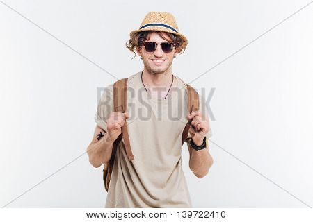 Portrait of cheeful happy young man with backpack over white background