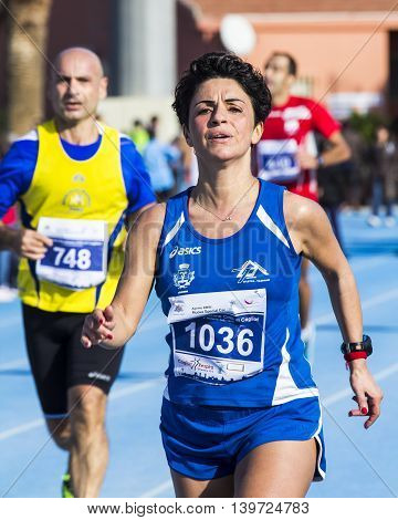 CAGLIARI, ITALY - December 7, 2014: 7 ^ Half Marathon - Memorial Delio Serra - portrait of a woman who takes part in the race