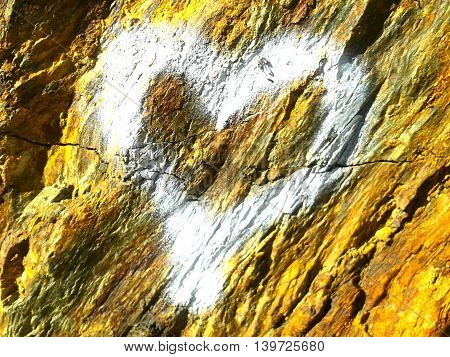 White heart spray painted on a rocky wall.