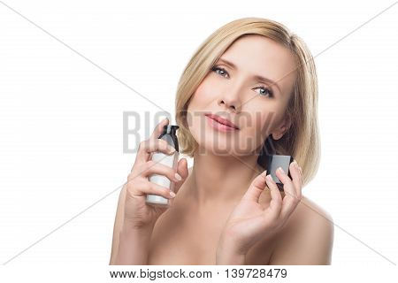 Beautiful middle aged woman with smooth skin and short blond hair applying face serum. Beauty shot. Isolated over white background. Copy space.