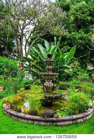 Mexican fountain in beautiful lush green garden
