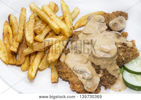 Schnitzel with mushroom sauce and french fries on a white background in the restaurant