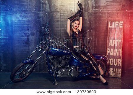 Biker girl posing sitting on the hard blue motorbike.
