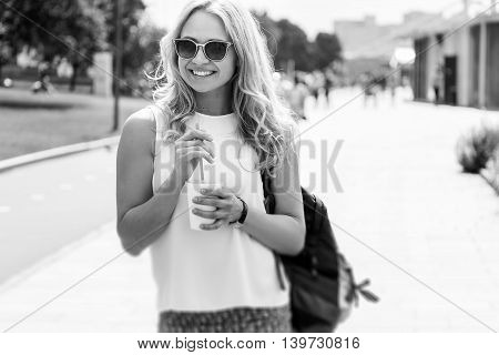 Black-and-white image of beautiful woman in sunglasses and with cup of drink in hand on blurred urban background. Image with tilt-shift effect