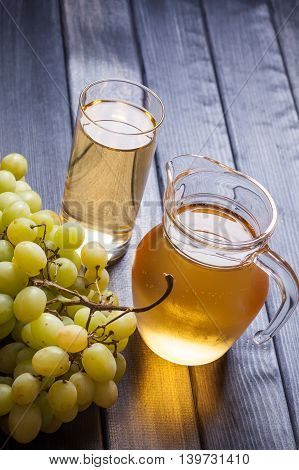 Fresh grapes and freshly squeezed juice on rustic wooden table, harvest time still life
