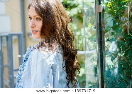 Portrait of brunette young woman in profile with long wavy hair outdoors