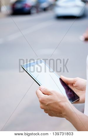 Female hands holding tablet on street in sunny day