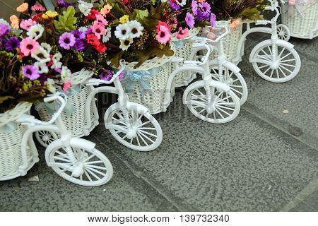 small toy bicycle with flowers in a basket on a cobblestone street. Postcard Greetings