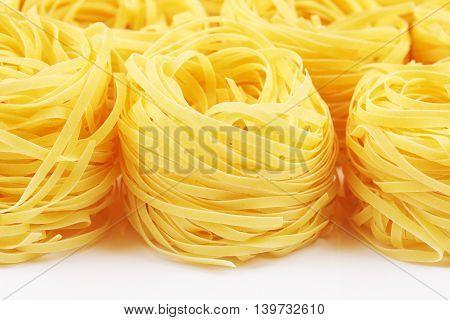 raw pasta tagliatelle nest lying on table