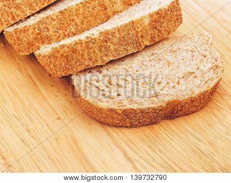 sliced wholegrain white bread lying on cutting board