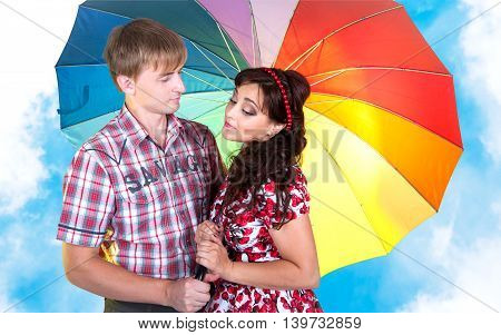 Beautiful couple man and woman standing under a multicolored umbrella against the blue sky