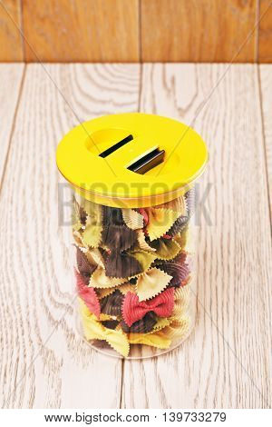 raw bow-knot pasta of different color in plastic container
