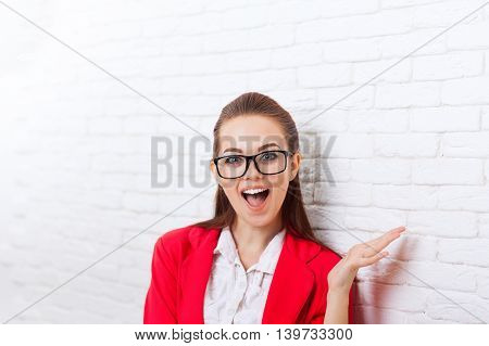 Businesswoman excited wear red jacket glasses happy smiling business woman over office wall