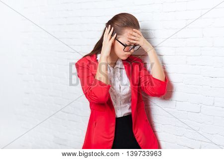 Businesswoman hold hands on head, ache, pain depressed wear red jacket glasses stressed business woman over office wall