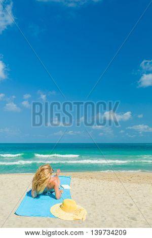 Woman in bikini suntannint at the tropical beach