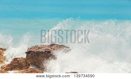 Rocky beach on Lefkada coast. Detail of breaking waves on beach, Lefkada, Greece waves crashing among rocks