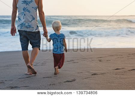 Happy family - barefoot father holds baby son hands walk with fun along sunset sea surf on black sand beach. Travel active parents lifestyle people activity on summer vacations with children.