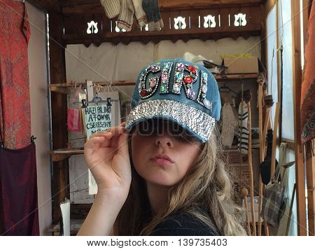 Romania, August 26, 2015, Corund, Transylvania, Young Girl selecting a special hat