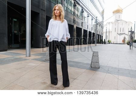 Serious blonde woman standing in full growth on street city and looking into distance