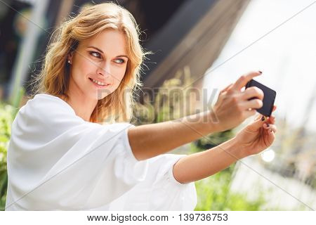 Portrait of smiling young woman making selfie photo in park on sunny summer day