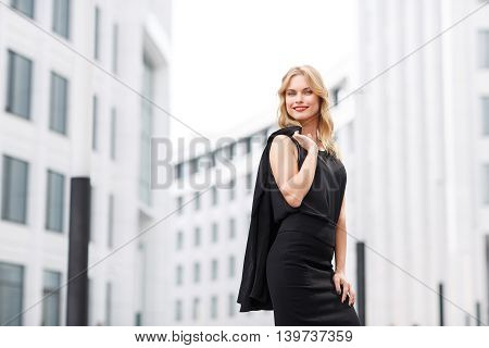 Smiling blond lady in black blouse and skirt standing near office building or business centre