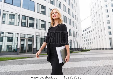 Portrait in motion of graceful confident business woman with laptop goes to meeting