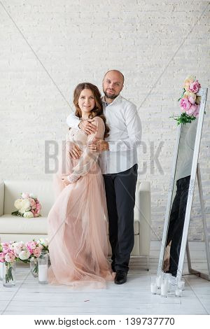 Portraint Of Pregnant Woman And Her Husband At Studio