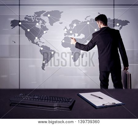 A young office worker drawing on world map and connecting dots with lines, presenting marketing sterategy at office environment concept