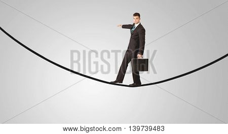 A confident smiling salesman balancing on black wire in clear grey empty space concept