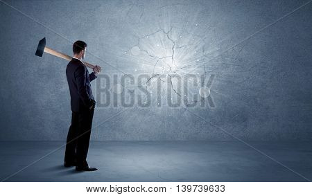 Business man hitting grungy wall with a hammer