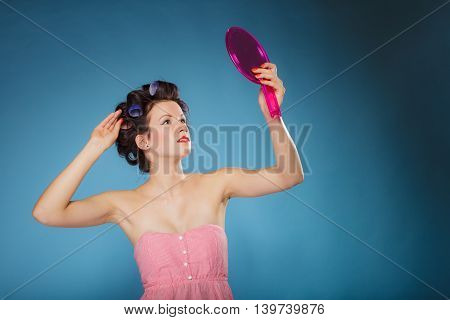 Girl Styling Hair With Curlers Looking In The Mirror