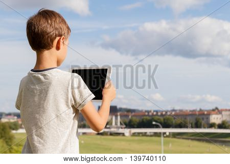 Smiling boy hold tablet PC. Blue sky and city background. Back to school, knowledge, education, learning, technology, leisure concept