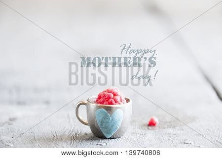 Ripe raspberry in a cup on the table and text Happy Mothers Day.