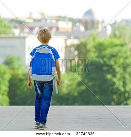 Boy with backpack on city street. Back to school, education, people, travel, tourism, leisure concept
