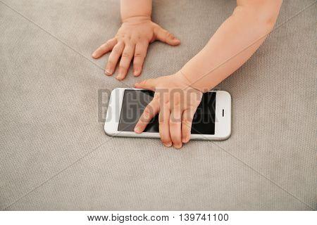 Baby touching telephone on sofa
