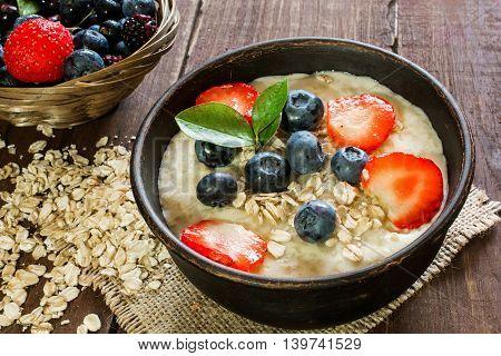 Oatmeal porridge in brown pottery bowl with ripe berries raspberries and blueberries in wicker bowl. healthy breakfast