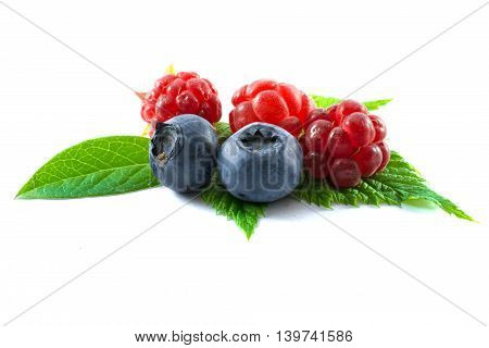 raspberries with blueberries and green leaves isolated on white background
