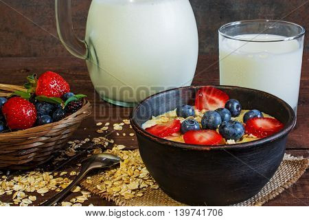 Milk in a jug and oatmeal porridge with glass of milk in a pottery bowl with fresh ripe berries in a wicker bowl standing on canvas on wooden table. healthy breakfast