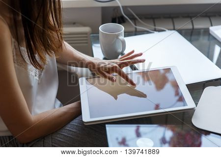Young brunette girl sitting at the table and touching screen of white modern laptop indoors