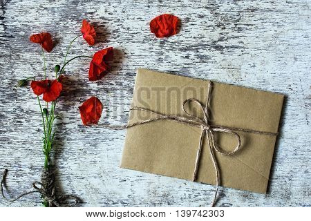 bouquet of wild poppy flowers and rope with brown envelope on white vintage wooden background. holiday gift concept