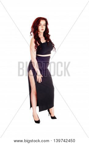 A pretty serious woman standing in a black long skirt and long red hair isolated for white background.