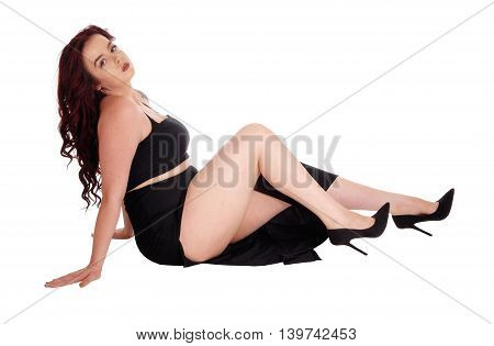 A beautiful young woman in a long black skirt sitting on the floor and dreaming isolated for white background.